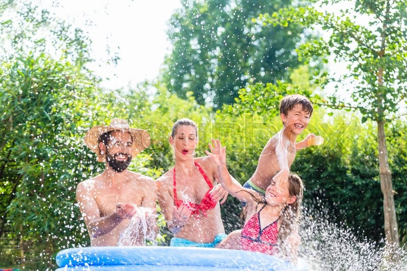 Family in garden pool splashing water cooling down, mother, father and kids having fun together, stock photo