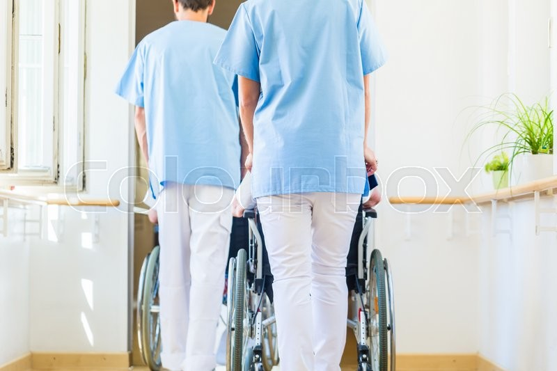 Nurses pushing seniors in wheelchair thru nursing home, stock photo