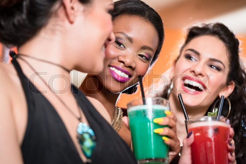 Beautiful girls in nightlife drinking cocktails and saying Cheers, stock photo