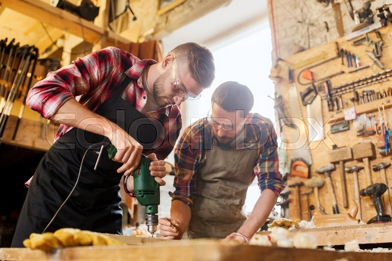 Profession, carpentry, woodwork and people concept - two carpenters with electric drill drilling wood plank at workshop, stock photo