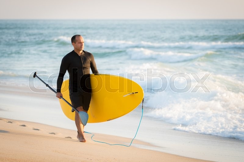 Man with his paddle board on the beach at sunset, stock photo