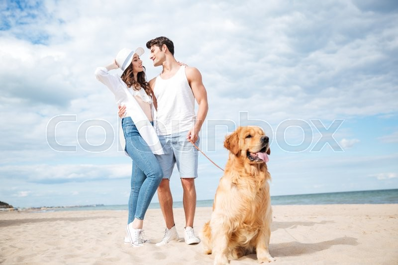 Dog sitting in front of happy young couple standing and hugging on the beach, stock photo