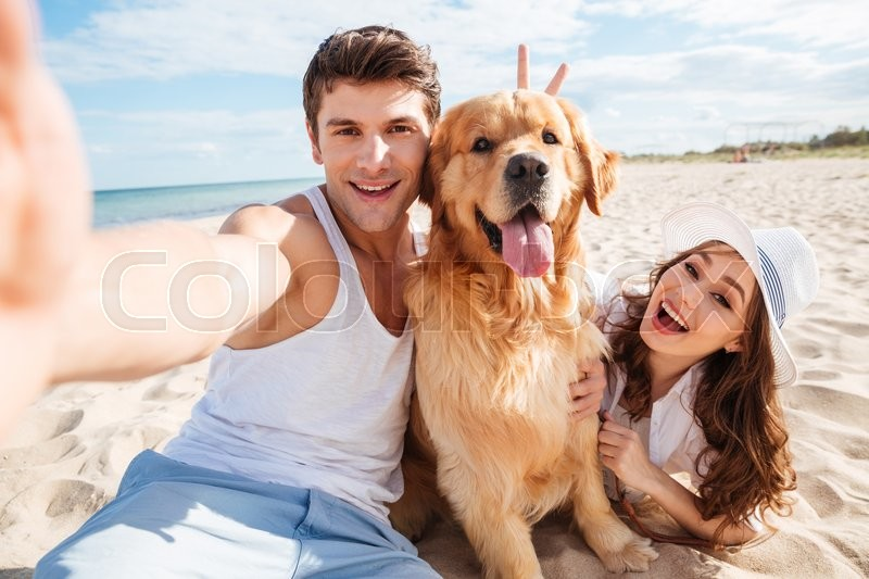Young happy couple with dog taking a selfie at the beach, stock photo