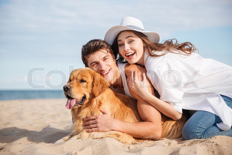 Happy young couple with dog laughing and having fun together on the beach, stock photo