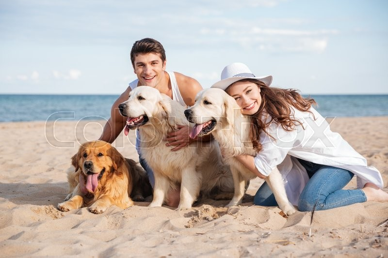 Cheerful young couple hugging three dogs and sitting on the beach, stock photo