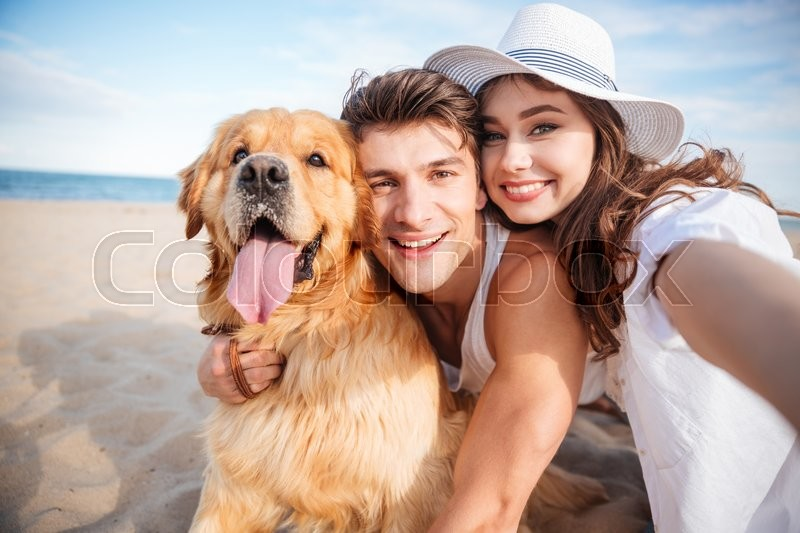 Portrait of happy young couple hugging their dog and smiling on the beach, stock photo