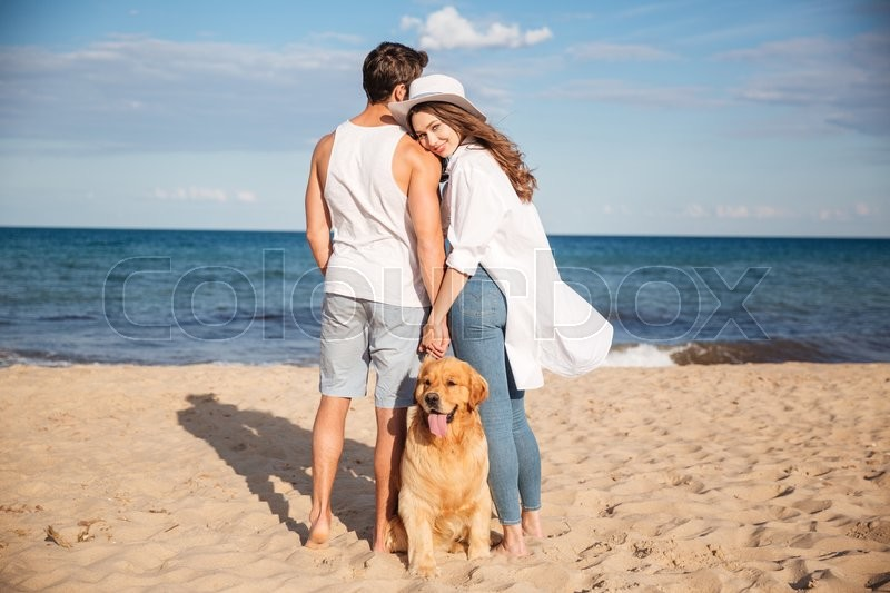 Happy young couple spending time together on the beach with their dog, stock photo
