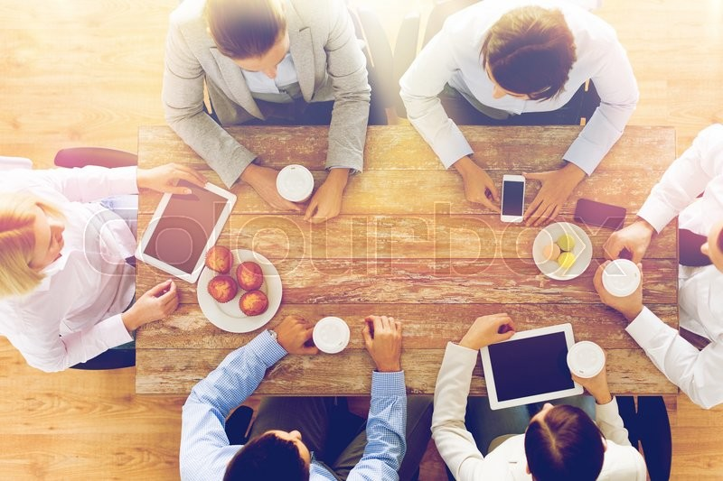 Business, people, break and team work concept - close up of creative team meeting and drinking coffee with muffins during lunch in office, stock photo