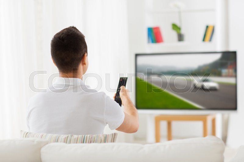 Leisure, technology, motorsports, sport and people concept - man with remote control watching car racing on tv at home, stock photo