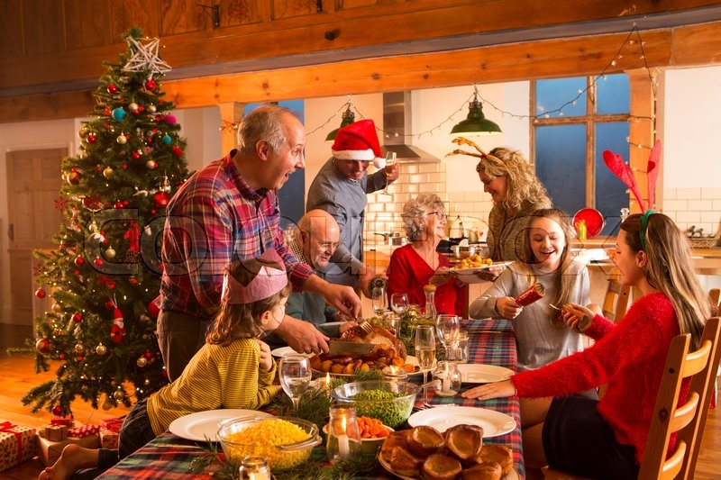 A large family are all helping serve Christmas dinner, stock photo