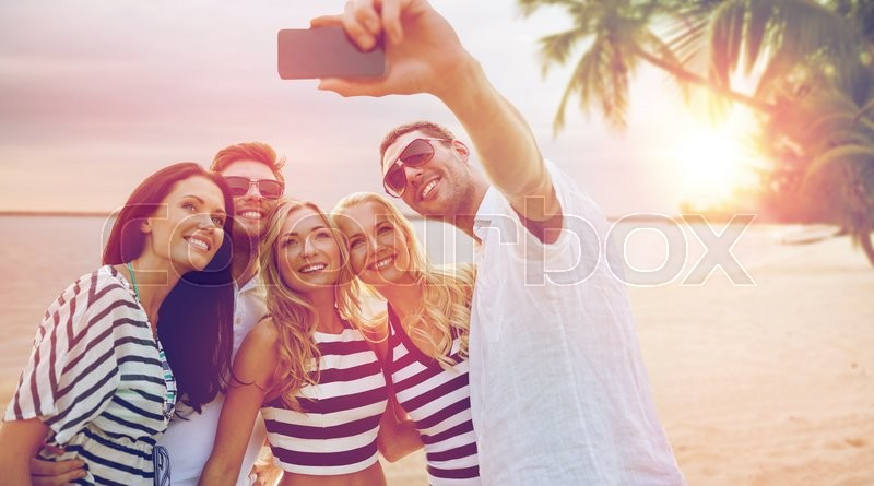 Summer holidays, travel, tourism, technology and people concept - group of smiling friends with smartphone photographing and taking selfie over exotic tropical beach background, stock photo