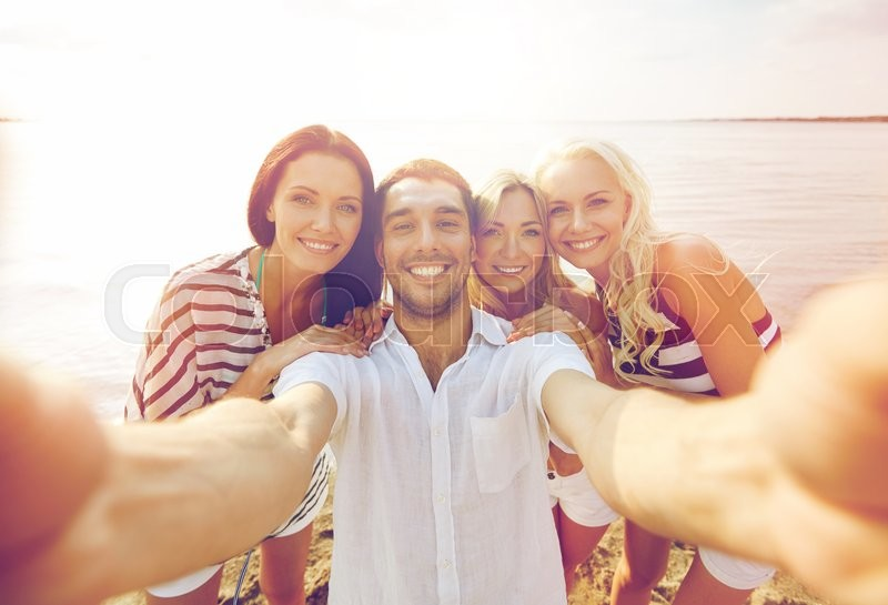 Summer, sea, tourism, technology and people concept - group of smiling friends with camera on beach photographing and taking selfie, stock photo