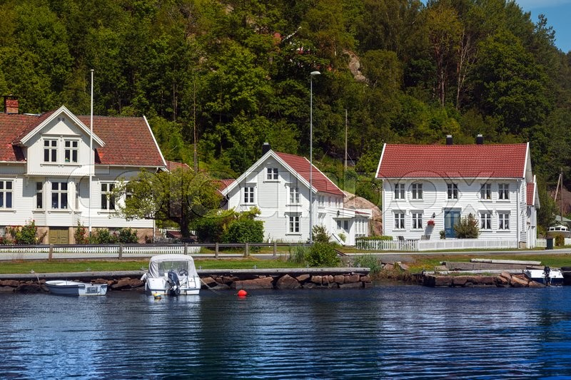 Traditional norwegian wooden house to stand at the lakeside and mountains in the distance - The house on the rock the ultimate refuge in a norwegian fjord ...
