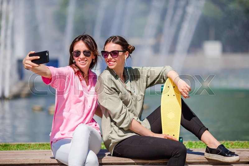 Caucasian girls making selfie background big fountain. Young tourist friends traveling on holidays outdoors smiling happy, stock photo