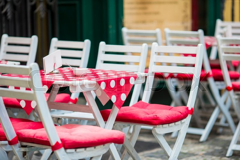White wooden tables with chairs at summer open air cafe terrace. View of empty outdoor cafe in Europe, stock photo