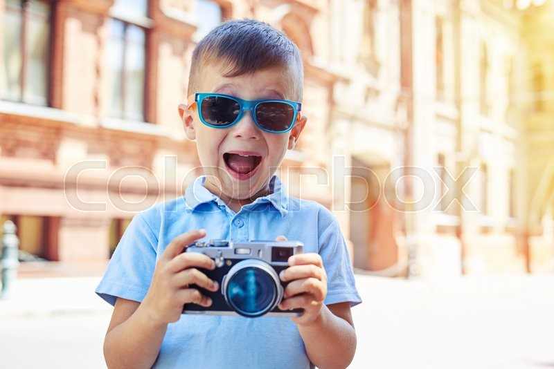Small boy in sunglasses is making excited face while holding a photo camera and trying to take a shot during walk in historical part of the city, stock photo