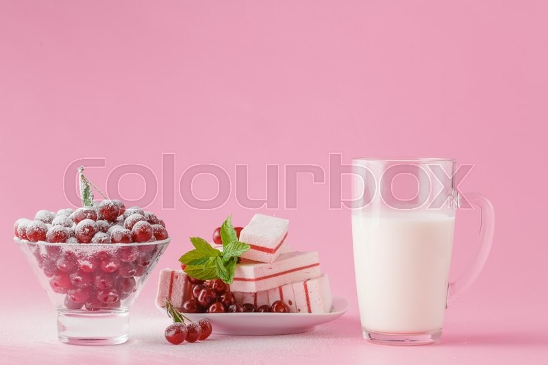 Glass of milk and wild cherry with sugar powder on pink background, stock photo