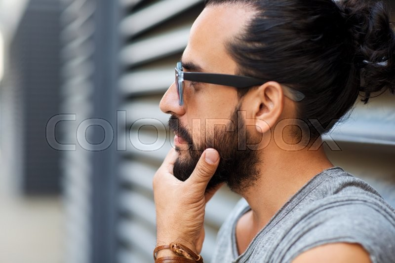 Lifestyle, emotion, expression and people concept - happy smiling man with sunglasses and beard on city street, stock photo