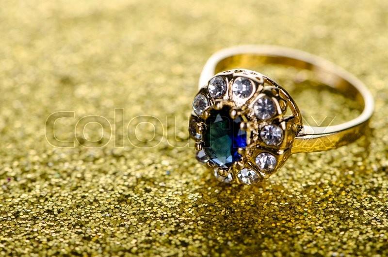 Jewellery ring against shiny background, stock photo