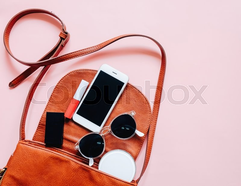 Flat lay of brown leather woman bag open out with cosmetics, accessories and smartphone on pink background, stock photo
