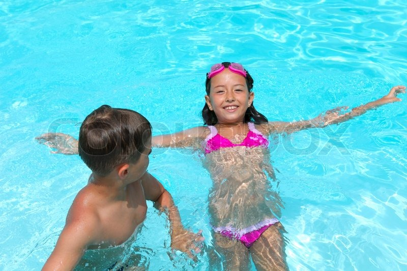 Happy Children Girl And Boy Relaxing On The Side Of A Swimming Pool Wearing Pink And Grey