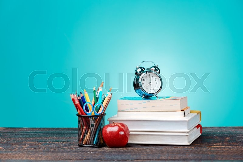 Back to School concept.School Books, colored pencils and clock on blue background, stock photo