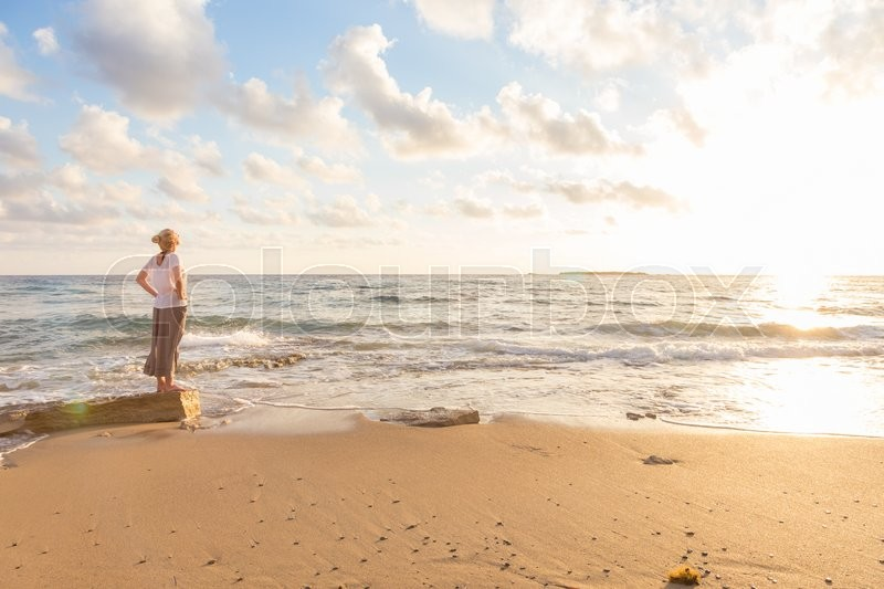 Relaxed woman enjoying sun, freedom and life an beautiful beach in sunset. Young lady feeling free, relaxed and happy. Concept of vacations, freedom, happiness, enjoyment and well being, stock photo