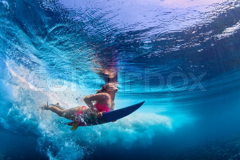 Stock image of 'Young active girl wearing bikini in action - surfer with surf board dive underwater under big ocean wave. Family lifestyle, people water sport adventure camp and beach extreme swim on summer vacation.'