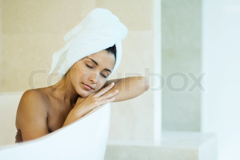 Woman in bathtub leaning on edge of tub, hair wrapped in