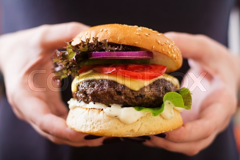 Big sandwich - hamburger burger with beef, cheese, tomato and tartar sauce in female hands, stock photo