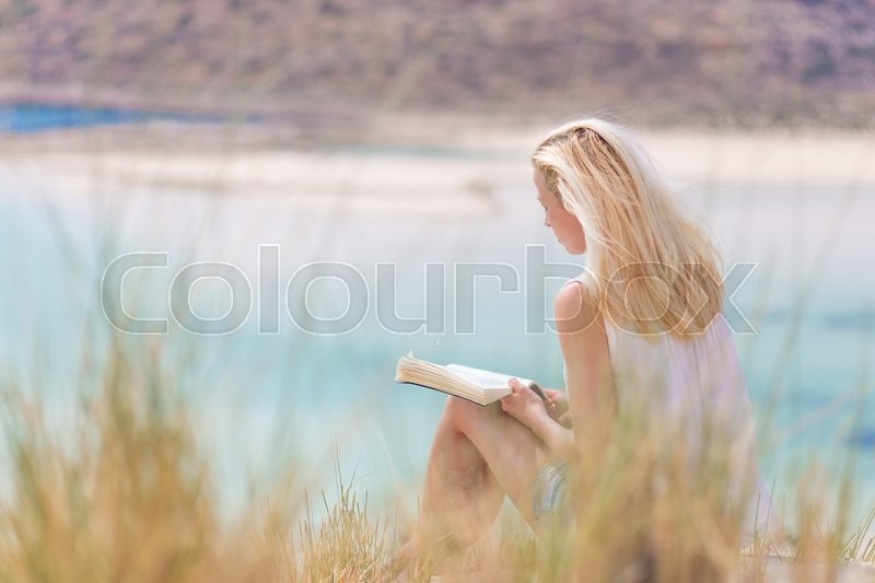 Relaxed woman enjoying sun, freedom and good book an beautiful sandy beach of Balos in Greece. Young lady reading, feeling free and relaxed. Vacations, freedom, happiness, enjoyment and well being, stock photo