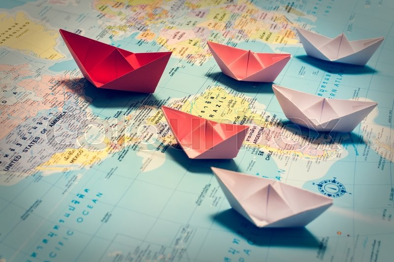 Paper boats following a red leader boat on world map. Concept for leadership, teamwork and winning success, stock photo