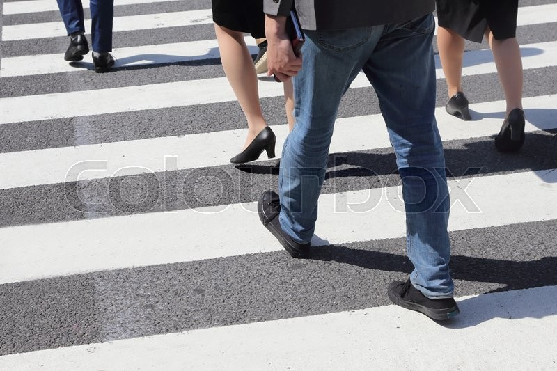 Close-up on unidentified people legs crossing street, stock photo