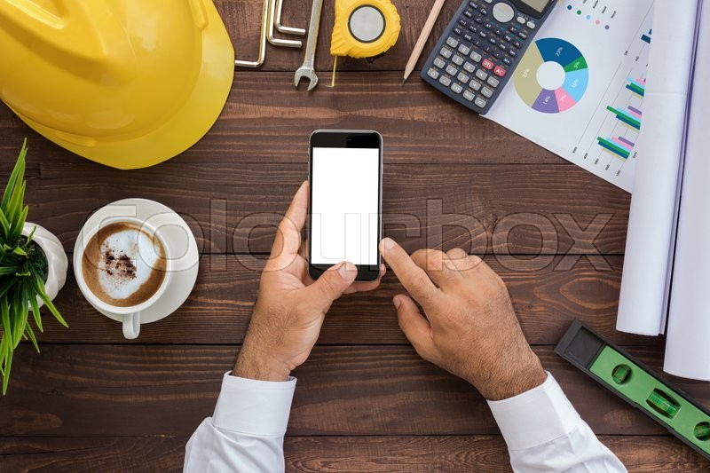Engineering using phone on his workspace top view, stock photo