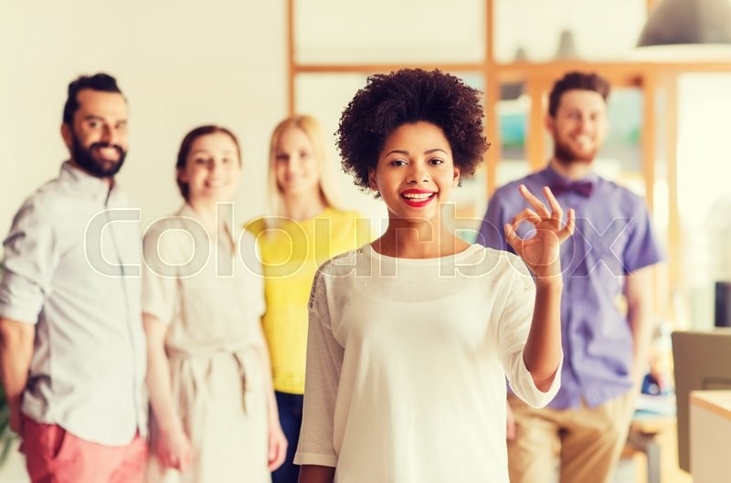 Business, startup, people, gesture and teamwork concept - happy young african woman showing ok hand sig over international creative team in office, stock photo