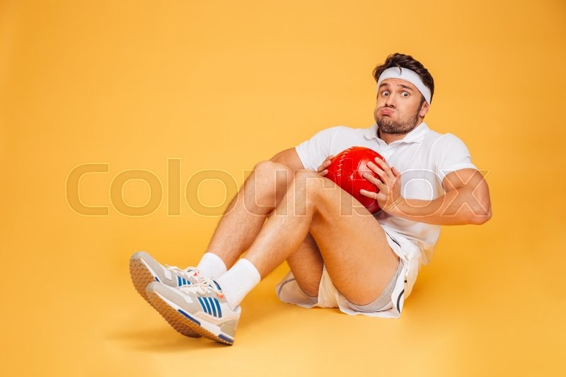 Funny sports man working out with fitness ball isolated on a orange background, stock photo