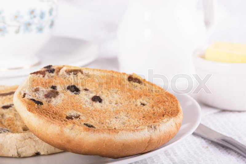 Tea with a traditional British teacake of raisins, sultanas and spices. Selective focus, stock photo