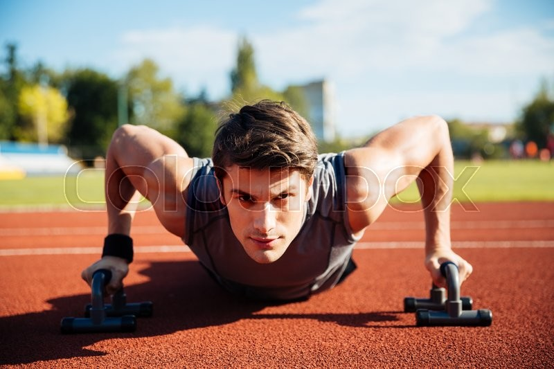 Young male athlete makes push ups on a racetrack at the stadium, stock photo