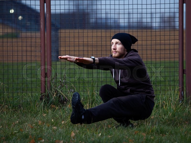Street workout - athlete man half turned performing one leg\'s squat ( pistol squat) outdoors, stock photo