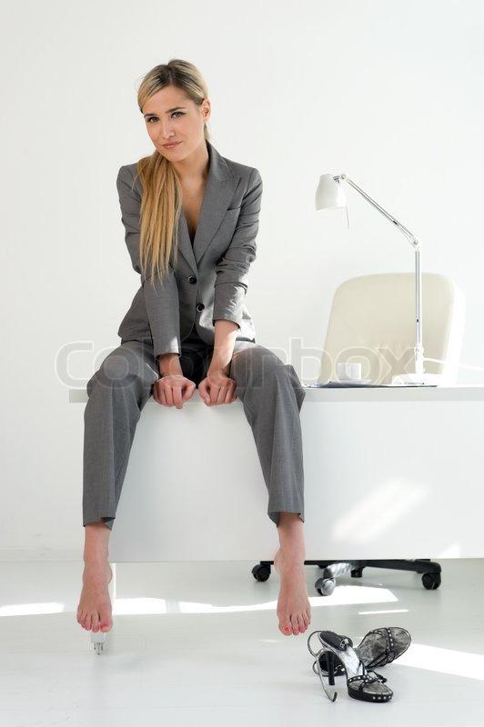 junge sch ne gesch ftsfrau auf dem tisch im b ro sitzen. Black Bedroom Furniture Sets. Home Design Ideas