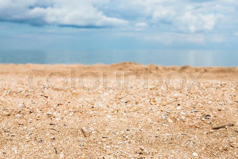 Foreground focus - sand and shelly beach close up and white clouds over blue sea. Coasline of Sea of Azov, Temryuk bay, Golubitskaya resort, Taman peninsula, Kuban, Russia, stock photo