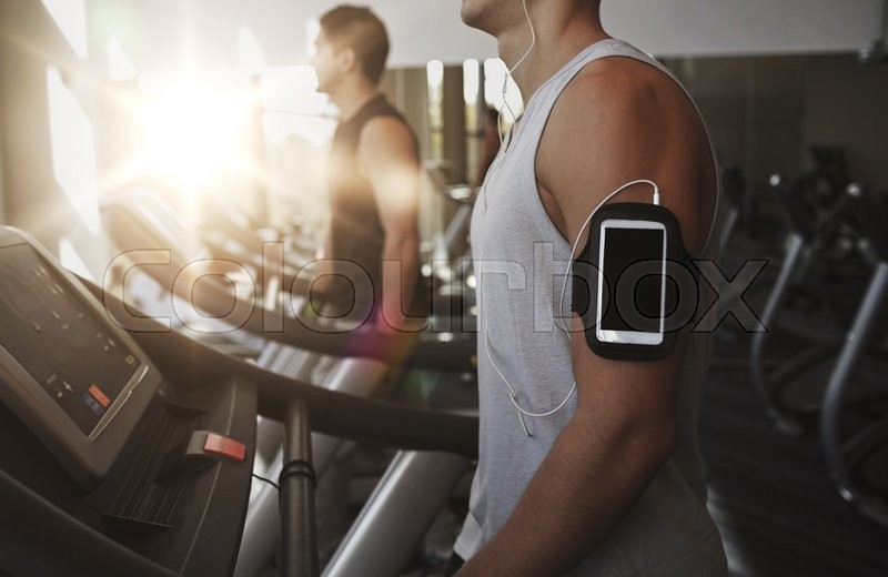 Sport, fitness, lifestyle, technology and people concept - man with smartphone and earphones exercising and listening to music on treadmill in gym, stock photo