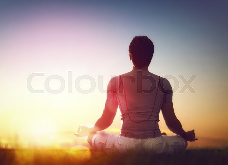 Young man enjoying meditation and yoga on green grass on sunset sky background, stock photo