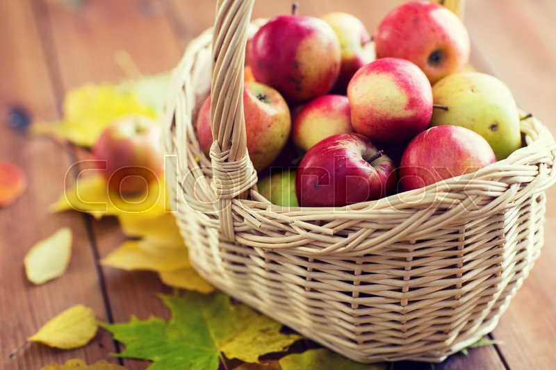 Gardening, season, autumn and fruits concept - close up of wicker basket with ripe red apples and leaves on wooden table, stock photo