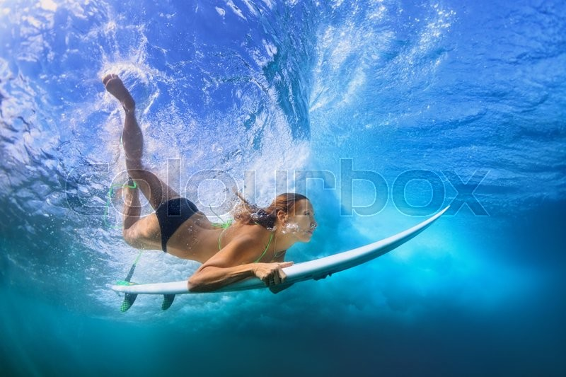 Young active girl in bikini in action - surfer with surf board dive underwater under breaking big ocean wave. Family lifestyle, people water sport adventure camp, beach extreme swim on summer vacation, stock photo