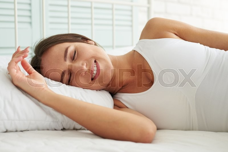 Beautiful brunette has a good sleep in her bed early in the morning at home, stock photo