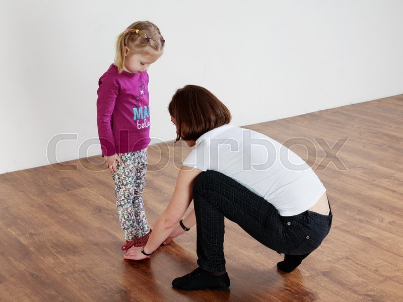 Children activity. Trainer showing leg position to a little girl , stock photo