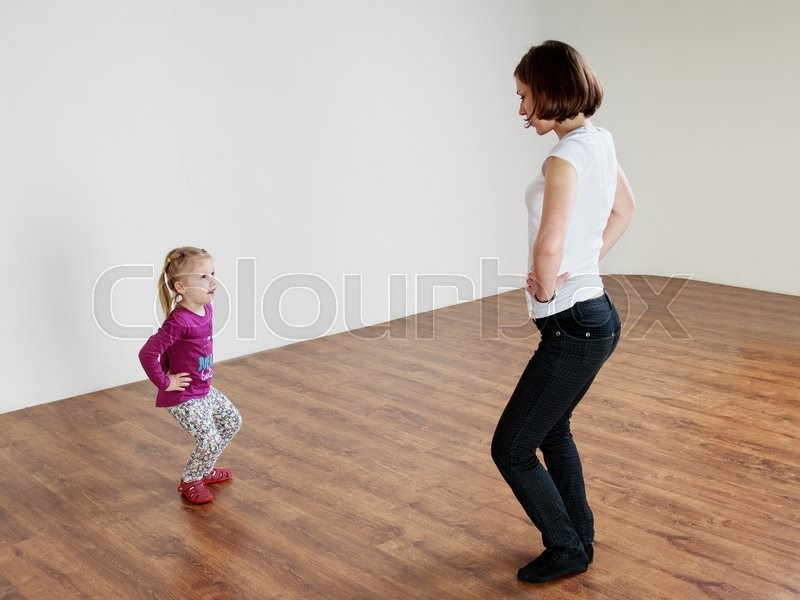 Children activity. Dancing classes. Trainer and a little girl are dancing at the gym , stock photo
