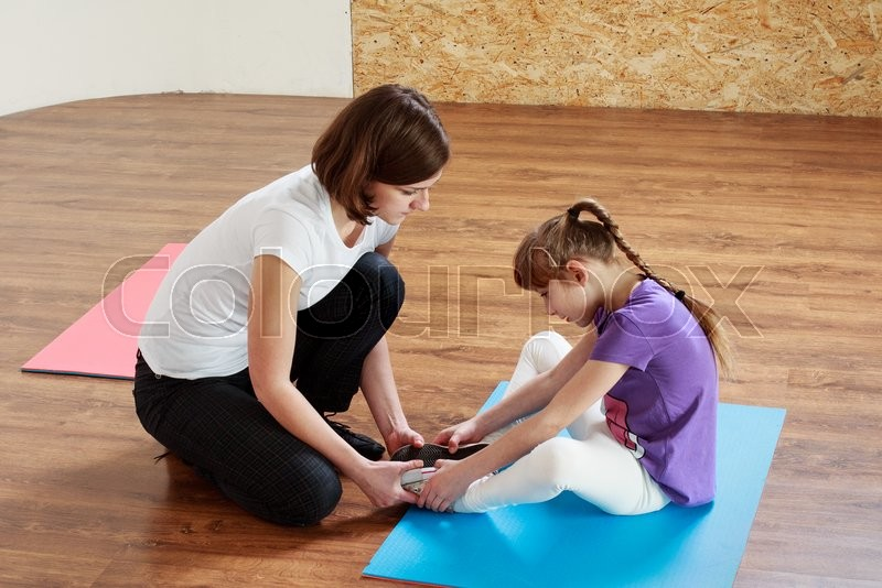 Physiotherapy for children. Trainer is helping a girl to do stretching, stock photo