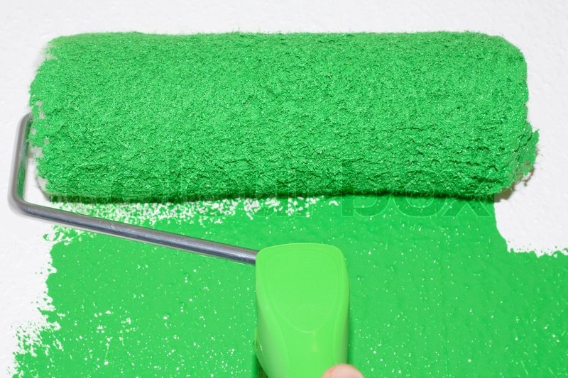 Green roller coloring white surface, stock photo